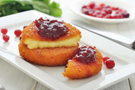 Breaded and baked camembert with cranberry sauce on white plate closeup photo