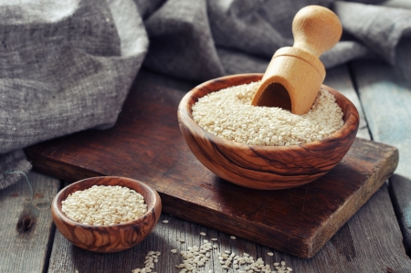 white sesame seeds: Sesame seeds in wooden bowl on wooden background Stock Photo