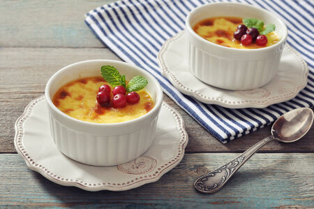 brulee: The creme brulee in ceramic baking mold with mint and berries on wooden table Stock Photo