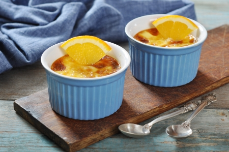 brulee: The creme brulee in ceramic baking mold with orange on wooden table