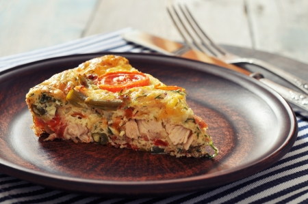 Frittata with Fresh Vegetables and chicken meat on plate photo