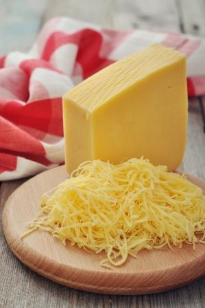 queso rallado: Queso rallado sobre tabla de cortar de madera de cerca Foto de archivo