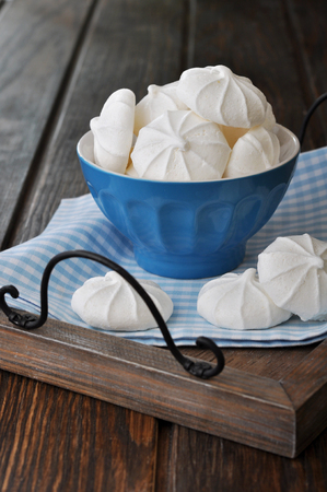 Meringue cookies in blue bowl on wooden tray Stock Photo