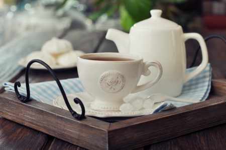 teapot: Cup of tea and teapot on wooden tray closeup