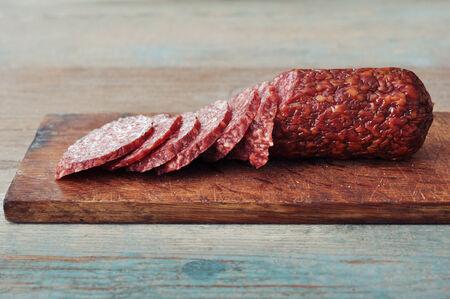 air dried salami: Sliced salami  on wooden cutting board closeup