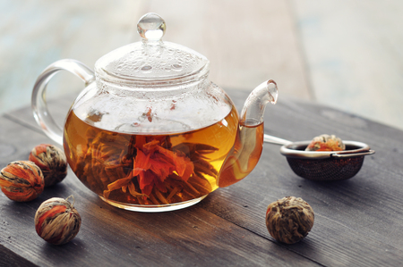 unfurl: Chinese flowering tea in glass teapot on wooden background Stock Photo