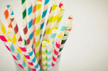 Striped drink straws of different colors in glass on light background