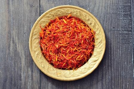 intense flavor: Saffron on golden plate on wooden  Stock Photo