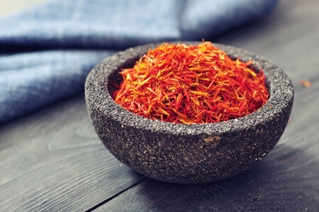 intense flavor: Saffron in stone bowl on wooden  Stock Photo