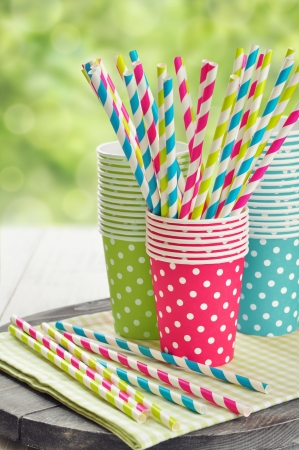 Kleurrijke papieren bekertjes en gestreepte rietjes voor verjaardagsfeestje.