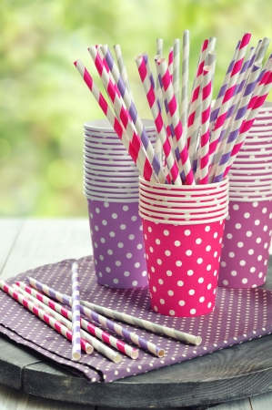 Colorful paper cups and striped straws for birthday party.  photo