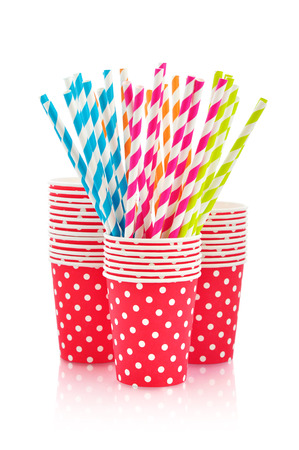 Colorful paper cups and striped straws for birthday party isolated on white
