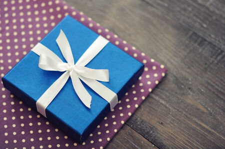 Blue elegant gift box on a wooden background photo