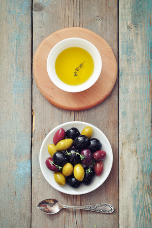 Different kinds of olives on plate with olive oil on wooden background