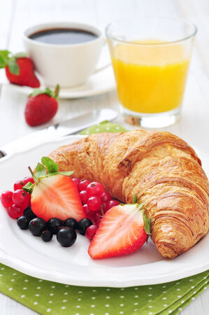 Fresh croissant with berries, coffee and orange juice closeup photo