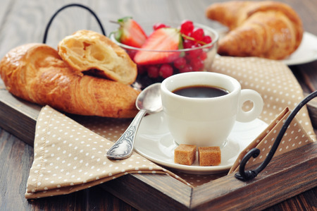 Cup of coffee with croissants and fresh berries on vintage wooden tray closeup photo