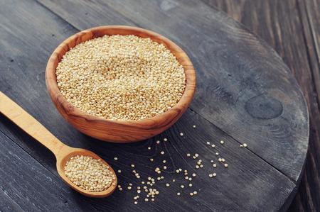 quinua: Semillas de quinua sin procesar en el taz�n de madera sobre fondo de madera de cerca