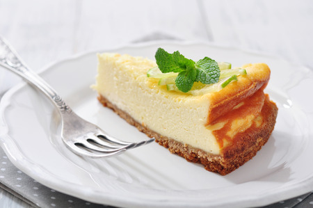 Cheesecake with lime and mint on plate closeup photo