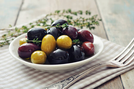 kinds: Different kinds of olives on plate with fork on wooden background Stock Photo