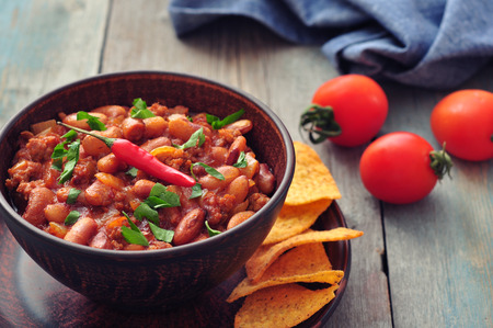 con: Chili Con Carne in bowl with tortilla chips on wooden table