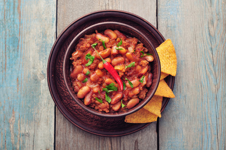 chilli: Chili Con Carne in bowl with tortilla chips on wooden background