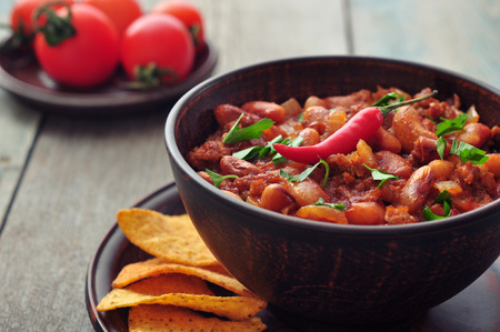 Chili Con Carne in bowl with tortilla chips on wooden background photo