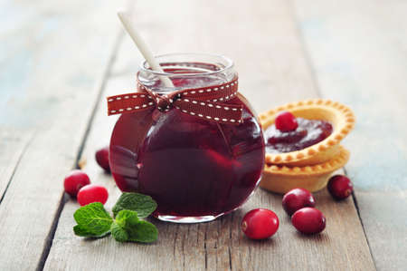 Cranberry jam in glass jar with fresh berry on wooden background photo
