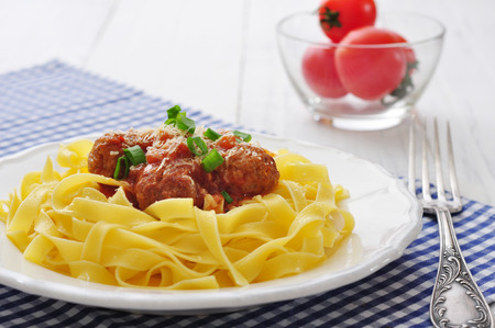 Meatballs with pasta and  parmesan in white plate on wooden background photo