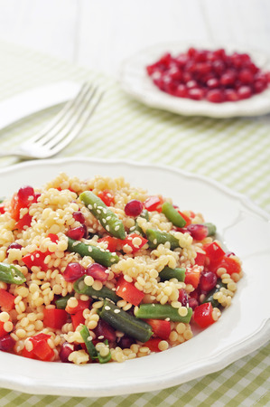Salad with couscous, sweet pepper, green bean, pomegranate and sesame on plate closeup photo