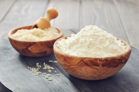 brown rice: Raw rice and flour in bowls with scoop on wooden background  Stock Photo