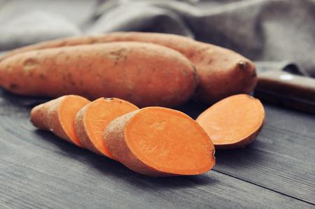 Rauwe zoete aardappelen op houten achtergrond close-up