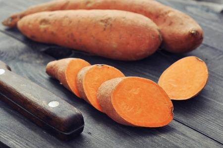 batata: Batatas crudas en el fondo de madera de cerca Foto de archivo
