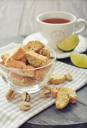 Fresh cantuccini with pistachios in glass bowl on wooden background photo