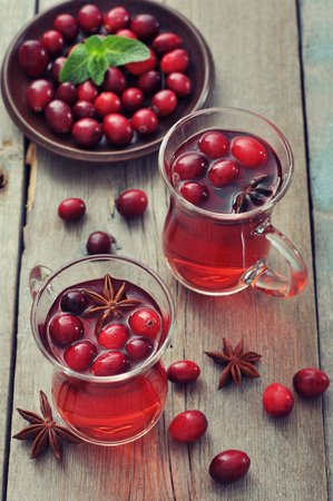 Mulled wine with fresh cranberry and cinnamon on wooden background photo