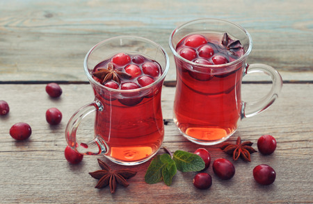 spiced: Mulled wine with fresh cranberry and anise on wooden background