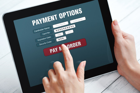 Female hands using touch screen device for online payment Stock Photo
