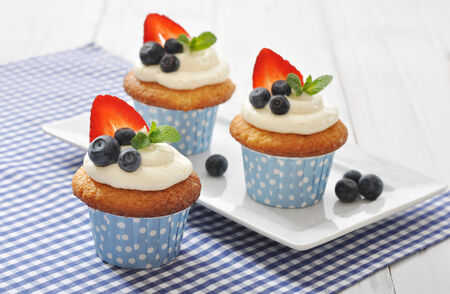 Cupcakes decorated with butter cream and fresh berries in polka dot cases on wooden background photo