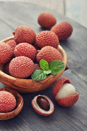lychee: Fresh lychee in bowl on a wooden background