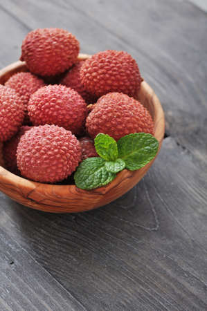 lichee: Fresh lychee in bowl on a wooden background