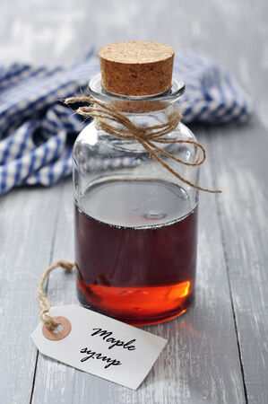 flavoring: Maple syrup in glass bottle on a wooden background Stock Photo