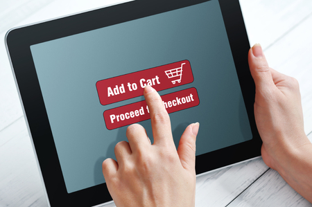 woman shopping cart: Female hands using touch screen device for online shopping