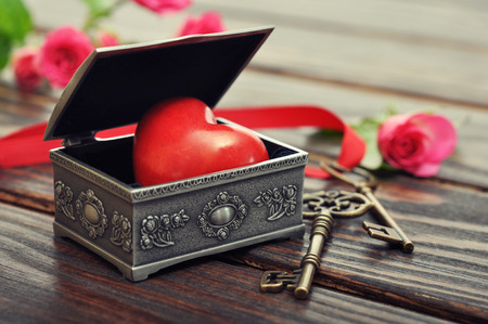 heart of stone: The stone heart in vintage tin gift box with keys and roses on wooden background