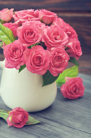 Bouquet of pink roses in vase on wooden background photo