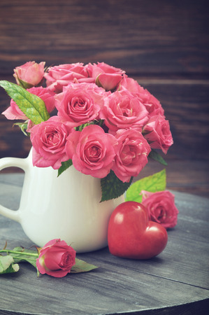 heart of stone: Bouquet of pink roses in vase with stone heart on wooden background