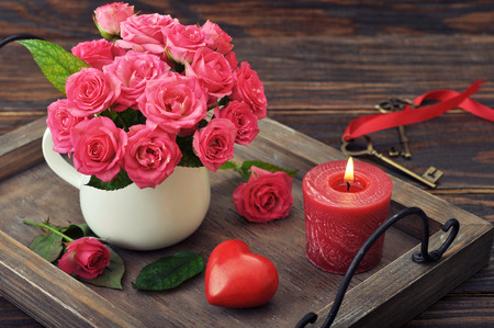 Rose bouquet with stone in shape of heart, keys and candle on wooden background. photo