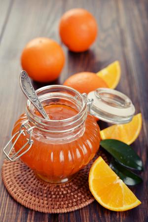 marmalade: Orange jam in glass jar on wooden background closeup