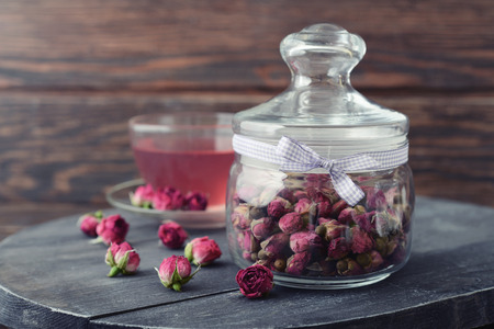 Tea rose flowers  in glass jar and tea on wooden background photo
