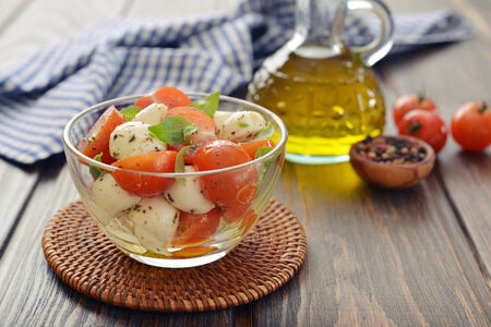 caprese salad: Caprese salad in glass bowl on wooden background
