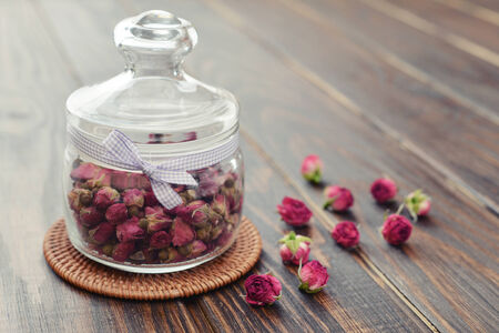 Tea rose flowers  in glass jar on wooden background photo