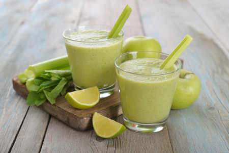 Smoothie of green apple, celery and lime on wooden background